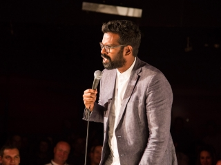 Romesh Ranganathan on stage at The Glee