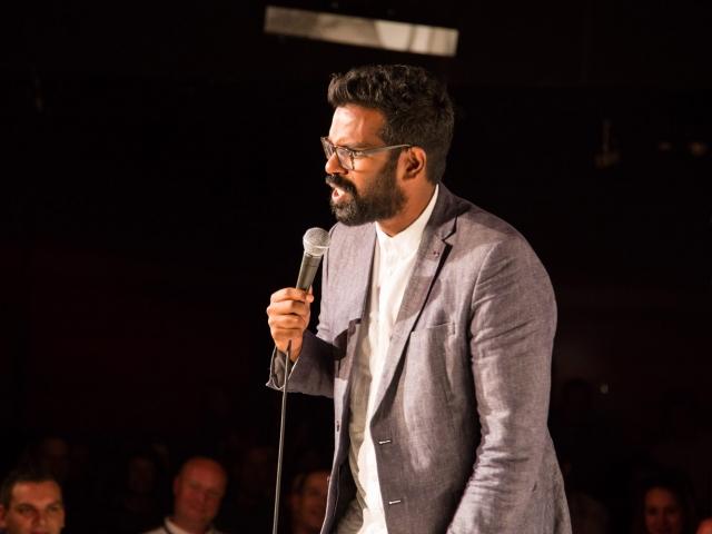 Romesh Ranganathan on stage at The Glee
