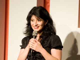 Shappi Khorsandi on stage at The Glee